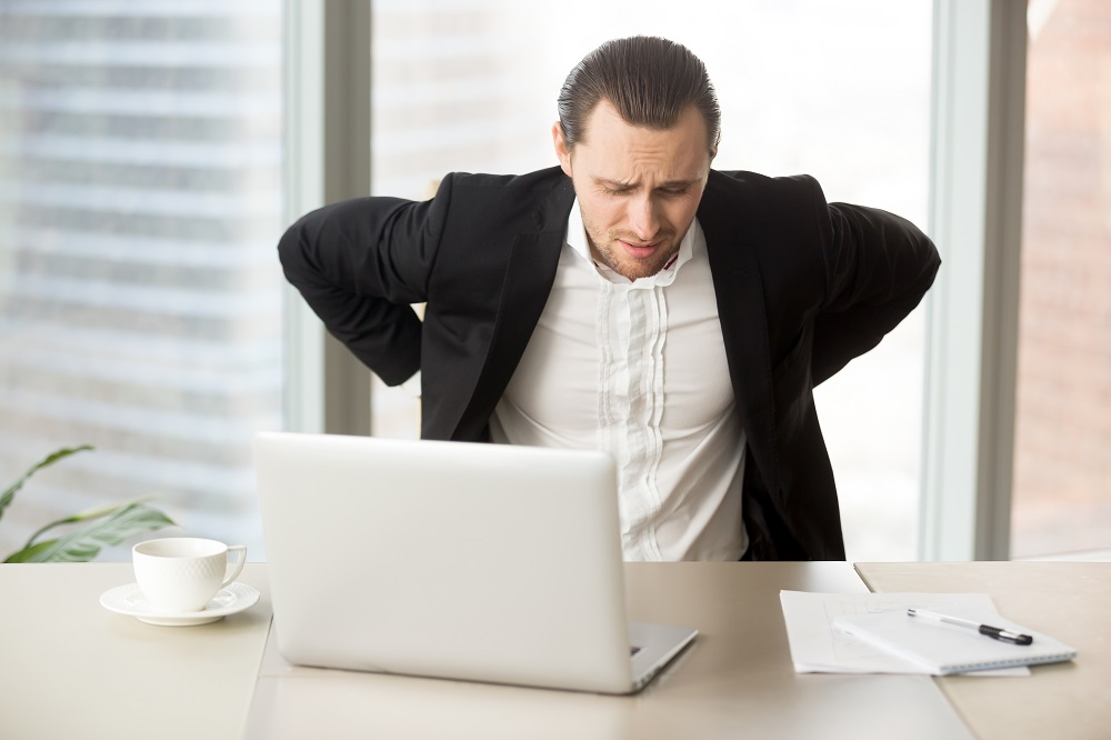 Man feels strong lower back pain after long hours work in office. Businessman suffering from backache at workplace. Office worker with painful face expression massaging and stretching his stiff waist